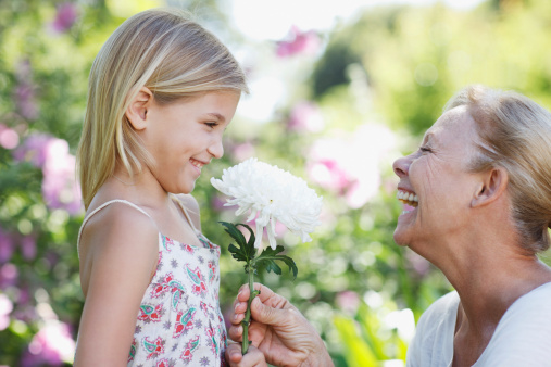 Grandmother giving flower to granddaughter in garden